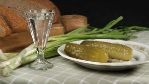 Фото: Натюрморт из рюмки водки, стрелок зеленого лука и соленых огурцов.
